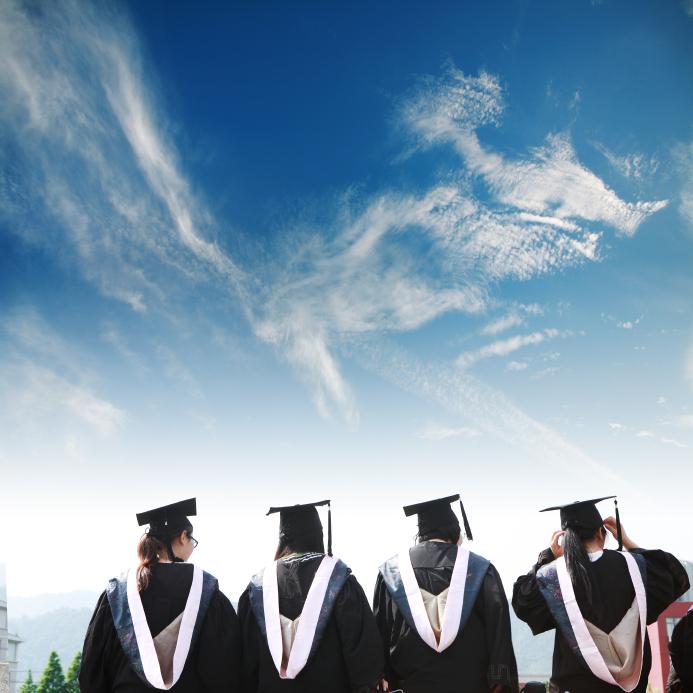 graduates with blue sky